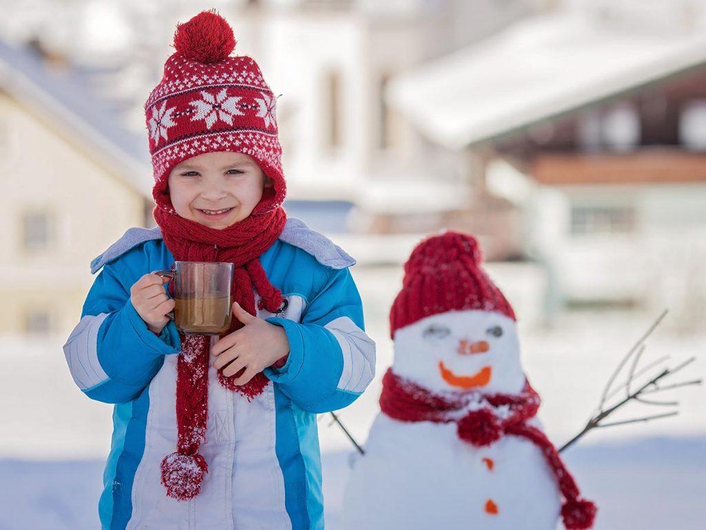 dieťa so šálkou kakaa v ruke v zime pred snehuliakom