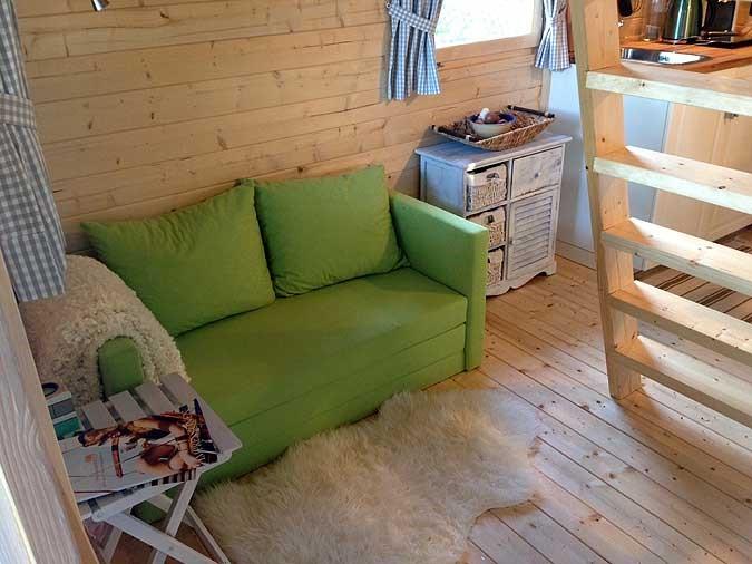 interiér záhradného domčeka Bunkie so zeleným gaučom