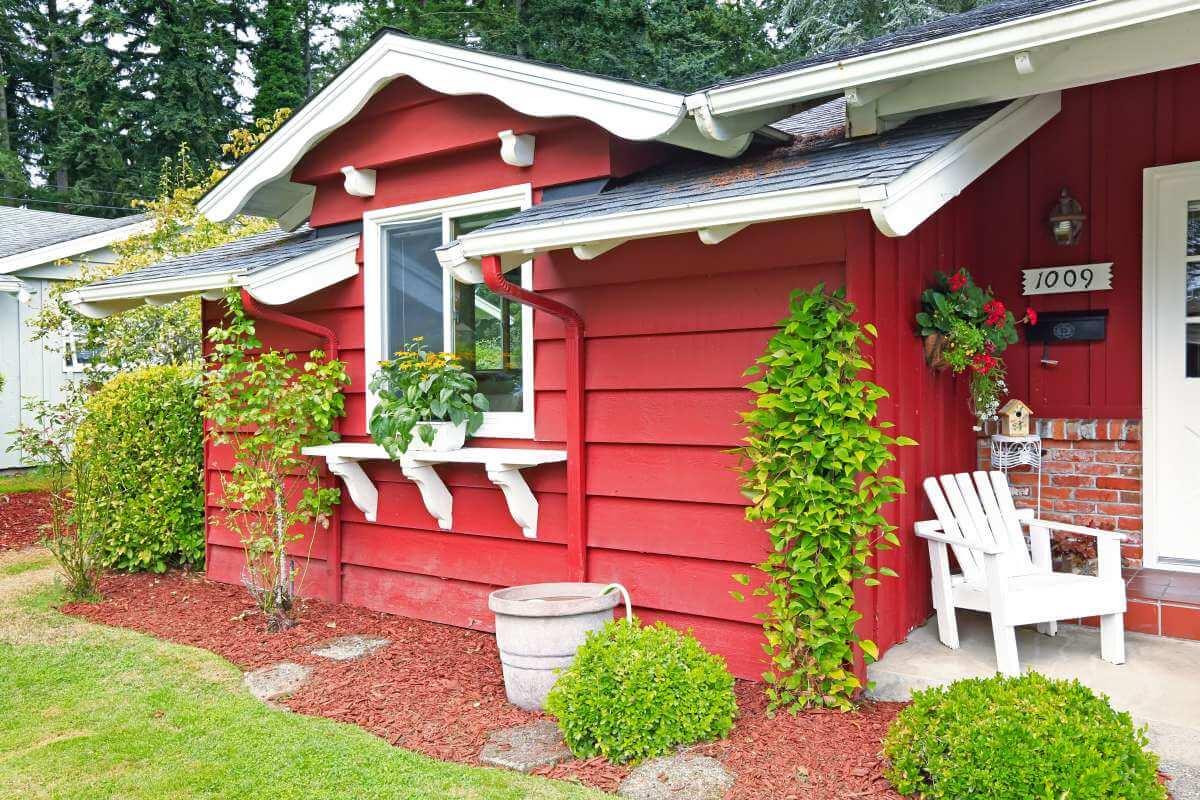 červený záhradný domček s kvetinami