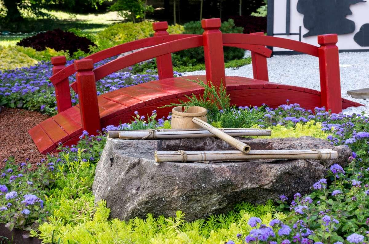 červený drevený mostík v japonskej záhrade