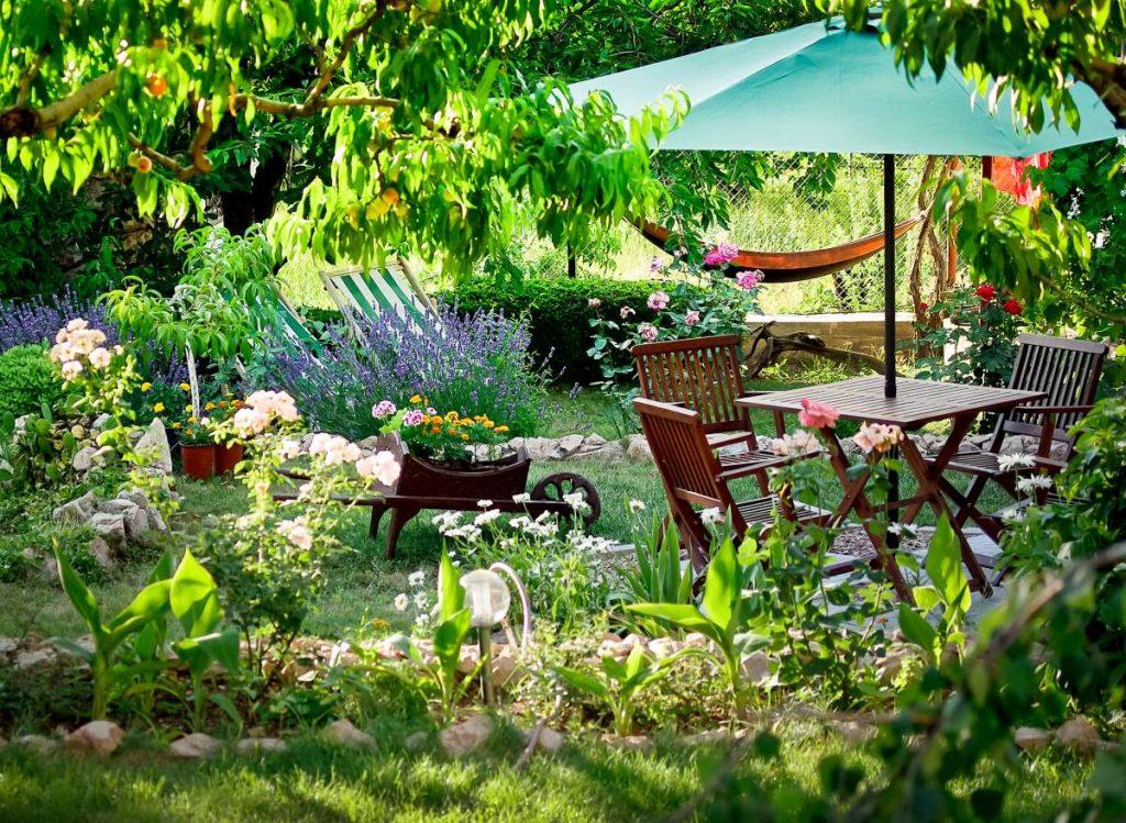 záhrada plná kvetín s dreveným posedením