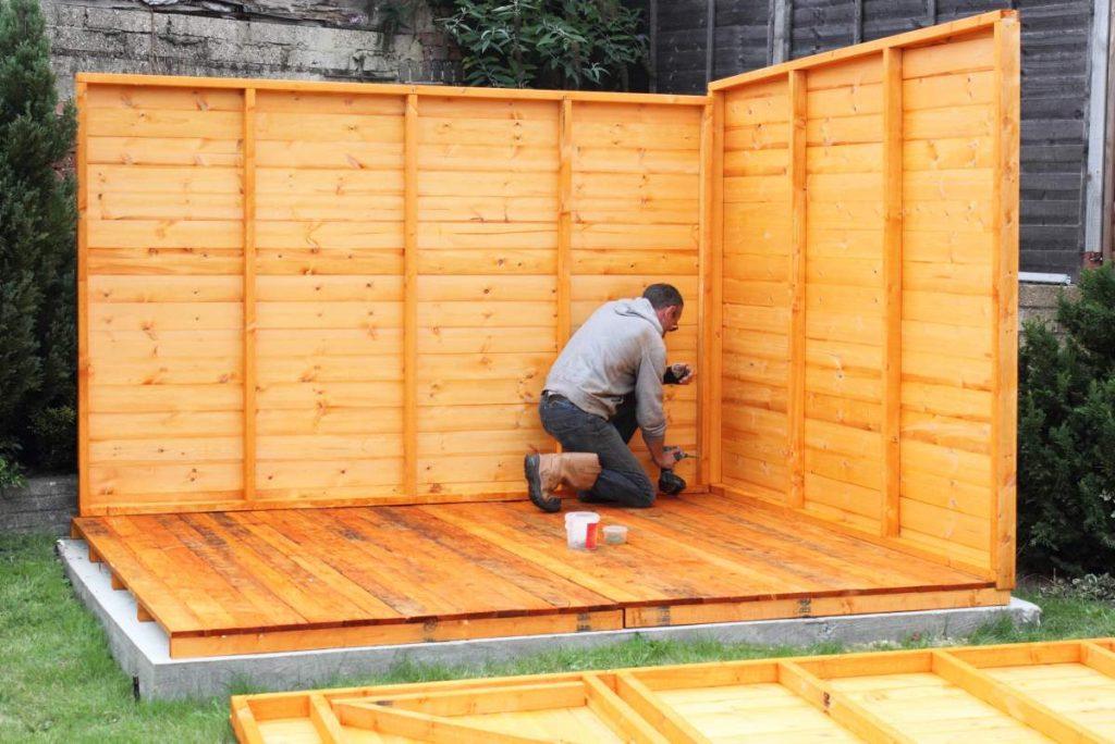 pracovník natiera drevo záhradného domčeka